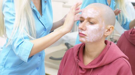 stylish bald woman at a beautician appointment. applying anesthetic cream to the face