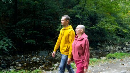 romantic couple man and bald woman walks in the autumn forest Stock Photo