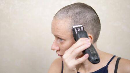 Glatzköpfige Frau rasiert sich den Kopf mit einem Elektrorasierer. Nahaufnahme, Textfreiraum Standard-Bild