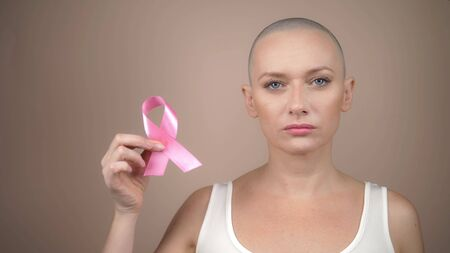 beautiful bald woman holds a pink ribbon in her hands. gentle pastel background. Stock Photo