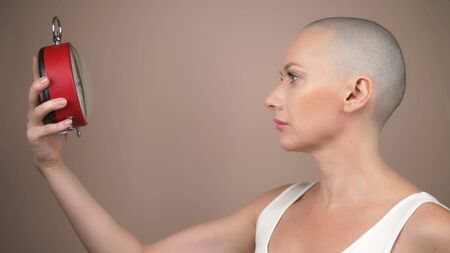 Portrait of shocked beautiful bald woman with an alarm clock on a beige background.