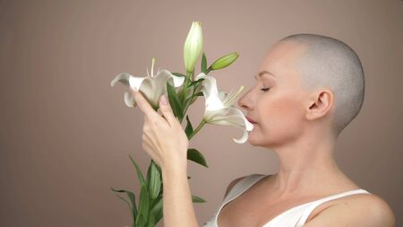 beautiful smiling bald girl sniffs a white lily. beige background, copy space