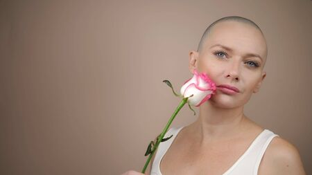 Beautiful smiling bald girl sniffs a pink rose. beige background, copy space