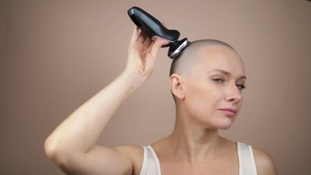 A young attractive bald girl shaves her head hair with an electric razor. beige background 스톡 콘텐츠