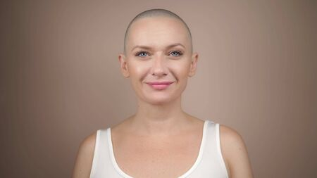 Beautiful bald woman looking at the camera and smiling. copy space, beige background