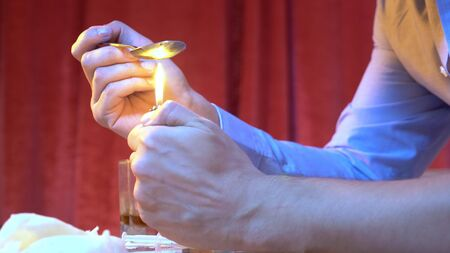 close-up. The preparations are prepared in a spoon with a lighter, on a red background. Social issue, addiction. Copy space Фото со стока