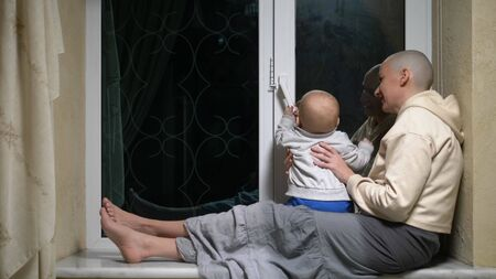 bald woman and baby sit together at the window in the evening. Reklamní fotografie
