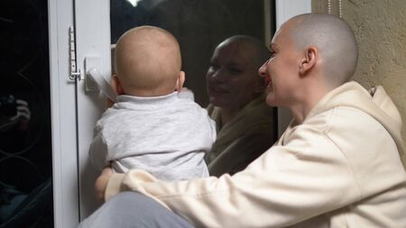 bald woman and baby sit together at the window in the evening.close-up