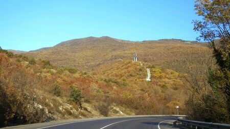 The view from the car on a hilly road, along magnificent mountains covered with bright colorful autumn trees. copy space. clear blue sky.