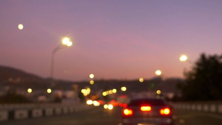 Blur background. traffic jam on the road in the evening, against the background of a beautiful lilac sunset sky, a bright moon is visible. Imagens