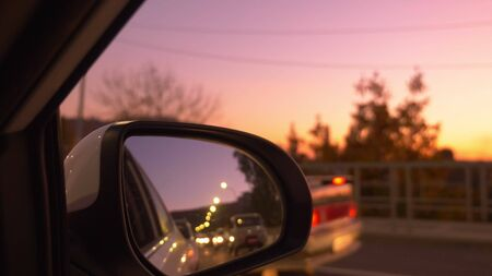view from the car window to the rear view mirror. Traffic jam in the evening, against the backdrop of a beautiful lilac sunset sky