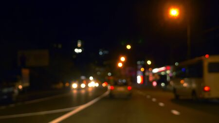 blurred background. view from the car window with blurry lighting of city traffic on the city streets at night Imagens