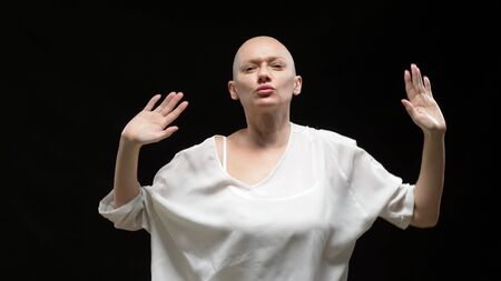 beautiful bald woman in white clothes is dancing on a black background 版權商用圖片