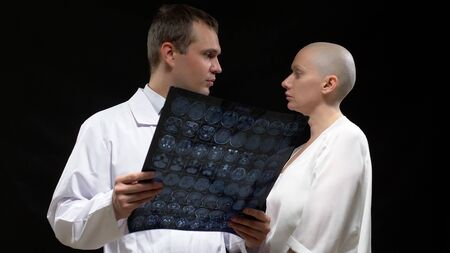 concept Oncological patient, bald woman and doctor man are viewing tomography results on black background.