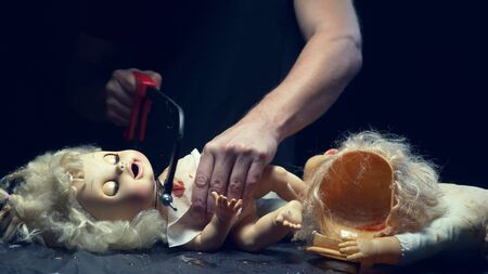 male hands cut off the head of an old doll. Halloween concept, violence, maniac