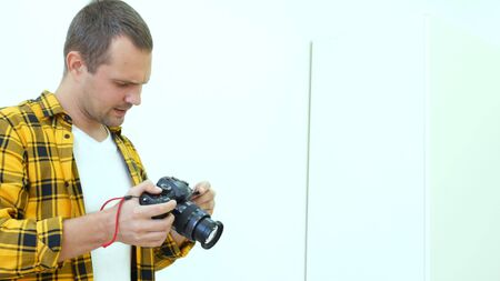 Handsome young man in a yellow checkered shirt, professional photographer holding a camera takes photos. Photographer at work. Imagens