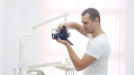 young handsome man Photographer takes pictures in a dental clinic. professional photographer at work. Stok Fotoğraf
