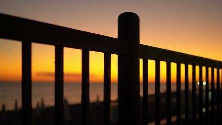 sunset by the sea on the embankment through the bars of the fence. Stock fotó