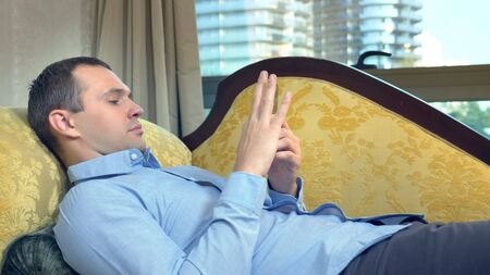 businessman resting on a sofa with a phone against a panoramic window from which skyscrapers are visible