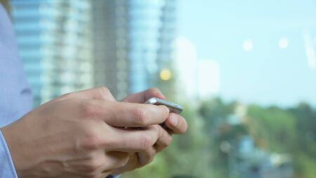 close-up. male hands use the phone against the background of a window from which skyscrapers are visible