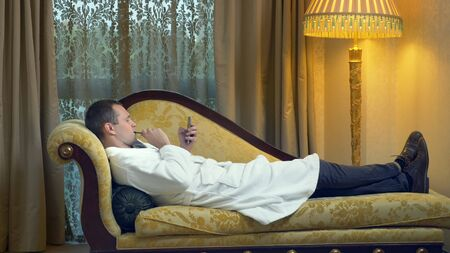 businessman in a bathrobe relaxes on a sofa with a phone and smokes a vape in the evening on the background of a window