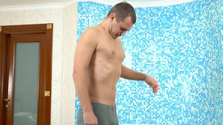 Caucasian young man measuring body with measuring tape while standing in the bathroom. humorous concept