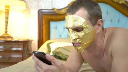 handsome man in a golden face mask is relaxing on a luxurious bed using a cell phone. close-up