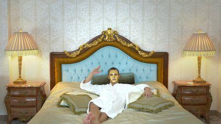Un bell'uomo con una maschera dorata e un accappatoio riposa su un letto lussuoso. guardando la telecamera