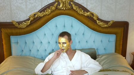 A handsome man in a golden mask and a bathrobe is resting on a luxurious bed smoking an electronic cigarette. looking at the camera. close-up