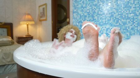 close-up. womans feet with finger dividers are covered with bath foam. woman doing pedicure taking a foam bath