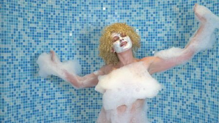 Happy and beautiful woman dancing with foam on her body while taking a bath with foam in a luxury apartment
