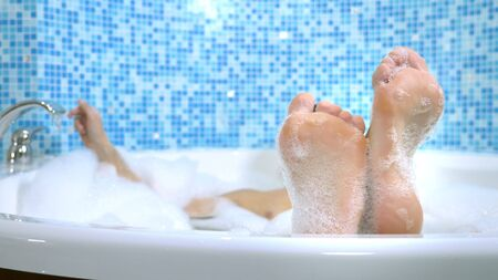 male feet of bath water. handsome man dancing with his feet while taking a bath with extensive foam