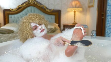 cheerful blonde woman does pedicure while taking a bath with foam