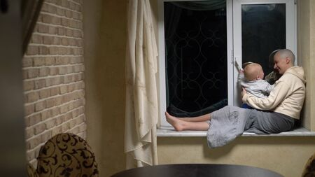 bald woman and baby sit together at the window in the evening. Фото со стока