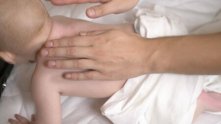Mens hands do massage on the back of a baby