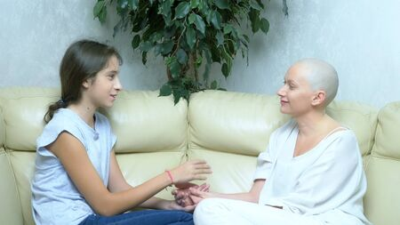 beautiful bald woman communicates with her daughter on the sofa in the living room
