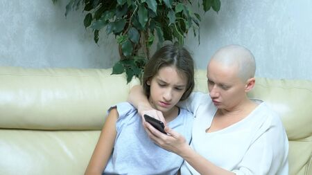 beautiful bald woman communicates with her daughter on the couch in the living room, they use a smartphone together Фото со стока