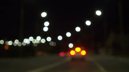 blurred background. view from the car window with blurry lighting of city traffic on the city streets at night.