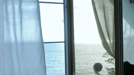 Transparent curtain on the window overlooking the sea, gently moved by the wind. Sunlight Foto de archivo