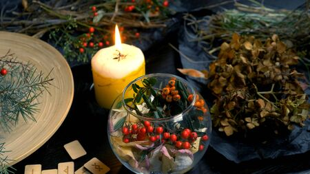 mystical background. dry herbs, runes, and a burning candle on the table