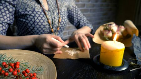 runic magic. master writes runic spell on parchment Stock Photo
