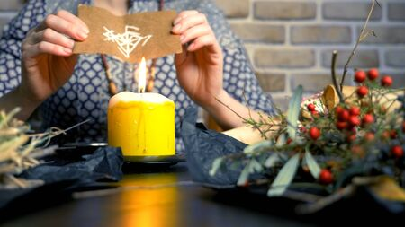 runic magic. master burns runic spell on parchment