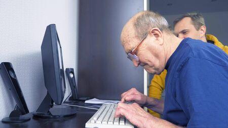 young man and seventy old man use computer together Reklamní fotografie