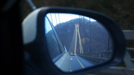 the reflection of the bridge in the rear view mirror while driving a car