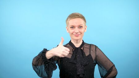 Elegant woman showing thumbs up. looking at the camera. blue background Фото со стока