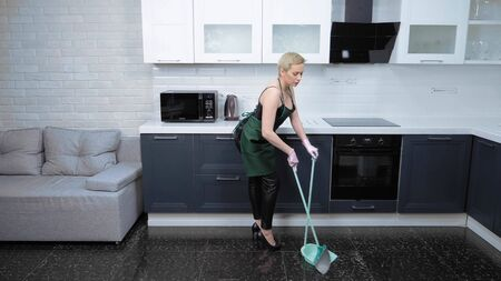 humor. woman in leather pants and apron sweeping the floor