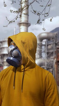vertically. A man in a respirator stands against a smoking factory chimney