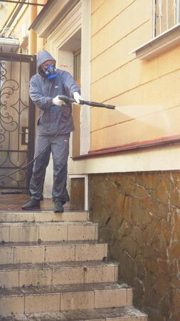 vertically. A man in the mask is cleaning a house outside with a high pressure washer