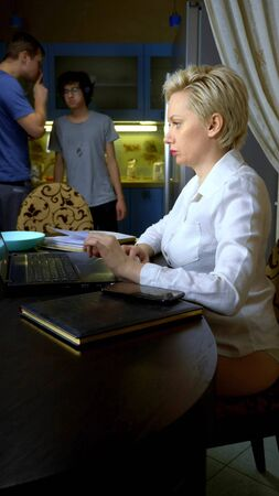 vertically. A woman in blouse working remotely from home in the kitchen