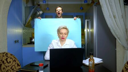 A woman works remotely from home in the kitchen, her husband is holding a blue background. humor